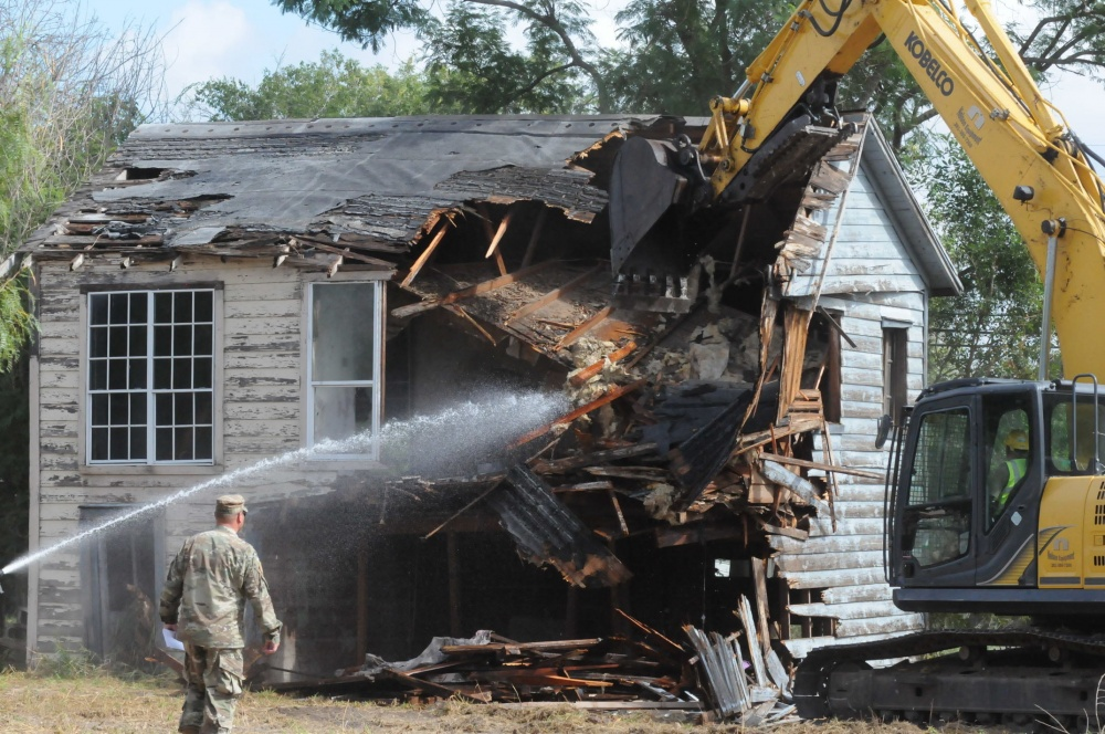 Courtesy Photo | Army National Guard Maj. Travis Urbanek, officer in charge of Operation Crackdown, coordinates the demolition of and abandoned home in Robstown, Texas, Aug. 11, 2017. Operation Crackdown, a component of the Texas Joint Counterdrug Task Force, supports local governments in removing dilapidated structures that are known to shelter the sale and use of illegal drugs. (U.S. Army National Guard photo by Staff Sgt. Yuliana Patterson)