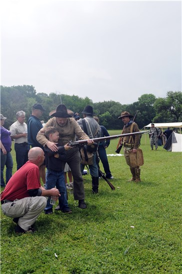 Aaron Black, an Austin native and father to Hal R. Black, watches as his son is assisted by living historian Lee R. Chesney in firing a rifle at the Texas Revolution and Civil War weapons demonstration at the 4th Annual American Heroes Celebration at Camp Mabry.