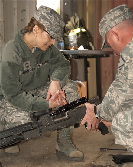 Chief Master Sgt. Denise Jelinski-Hall, senior enlisted adviser to the chief of the National Guard Bureau, watches a member of the Texas Air National Guard demonstrate the disassembly process for a M249 Squad Automatic Weapon at Camp Swift, near Bastrop, Texas, Feb. 9, 2013.
