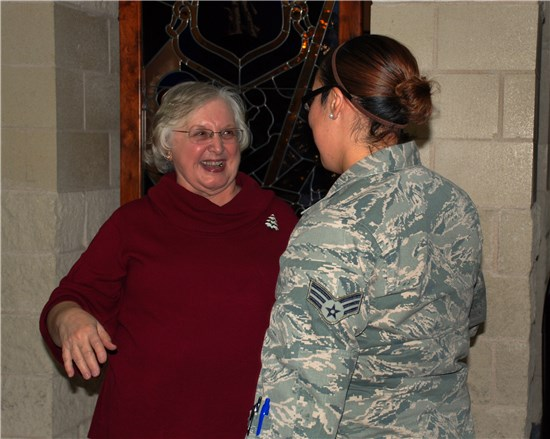 Ms. Gloria Sassman, the deputy human resources officer for the Texas Military Forces, greets a member of the Texas Air National Guard following Sassman's retirement ceremony on Camp Mabry, in Austin, Texas, Dec. 20, 2012.