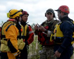 rom left: Melchor Fernandez, Luke Schott and Jeff Keuper from Federal Emergency Management Agency's Texas Task Force 1, discuss a search and rescue mission with a joint terminal attack controller from the 147th Air Support Operations Squadron, 147th Reconnaissance Wing, based at Ellington Field Joint Reserve Base in Houston, Texas