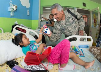 Senior Master Sgt. Arellano gives a Chilean girl a gift ans a smile during a visit to the Children's ward at the Leonado Guzman Hospital