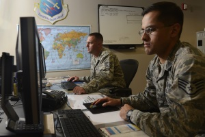 Photo of two soldiers working at computers