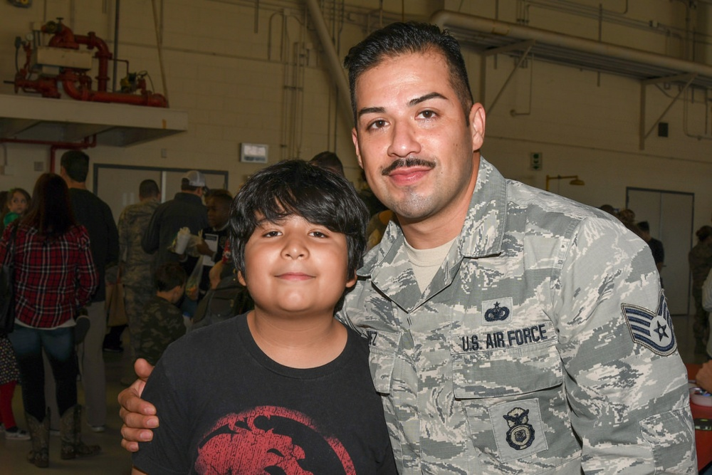 Photo By Tech. Sgt. Vanessa Reed | Staff Sgt. Juan Nunez a security forces specialist with the 136th Security Forces Squadron, Texas Air National Guard, and his son pose for a photo at the 136th Airlift Wing's Annual Children's Christmas party Nov. 20, 2016 at Naval Air Station Fort Worth Joint Reserve Base, Texas. (Air National Guard photo by Tech. Sgt. Vanessa Reed)