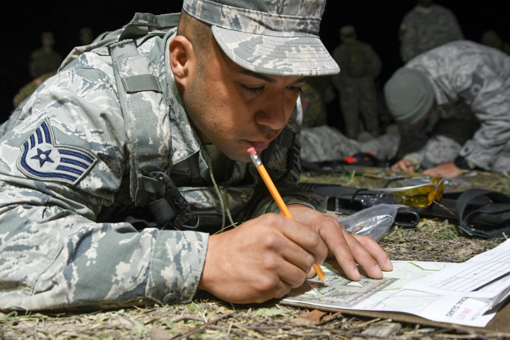 Photo By Senior Airman DeJon Williams | Air Force Staff Sgt. Juan Nunez, a security forces specialist with the 136th Security Forces Squadron, Texas Air National Guard, Fort Worth, Texas, plots points on his map during the land navigation event during the 2017 Texas Military Department Best Warrior Competition, March 2, 2017 at Camp Swift, near Bastrop, Texas. Land navigation tests the competitors ability to read maps, use a compass and other skills to traverse through unfamiliar terrain to different points throughout the course. (Air National Guard photo by Senior Airman De'Jon Williams)