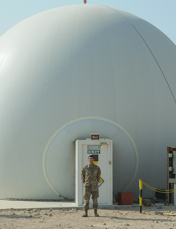 Sgt. Richard Bosquez, F Company, 2-149th General Support Aviation Battalion's acting facility chief at Udairi Landing Zone, poses in front of the Radome, which houses the Air Traffic Navigation, Integration, Coordination System at Camp Buehring, Kuwait, Oct. 19, 2017. F Co. Soldiers provide air traffic services and airfield management at multiple locations in both Kuwait and Iraq. (Photo by Capt. Stephen James)