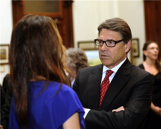 Texas Gov. Rick Perry visits with Taya Kyle, wife of slain Navy SEAL Chris Kyle, following the signing of Senate Bill 162 at the Texas State Capitol, in Austin, Texas, Aug. 28, 2013.