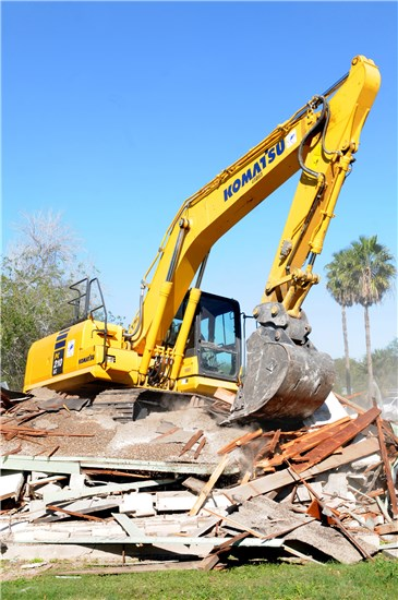 Tech Sgt. Carl White Jr., 147th Civil Engineers, 147th Fighter Wing, Texas Air National Guard, uses the heavy 45,000 pound Komarsu excavator to crunch rubble from a destroyed house into smaller pieces ready to be transported to a local landfill, Harlingen, Texas, Dec. 16, 2013.