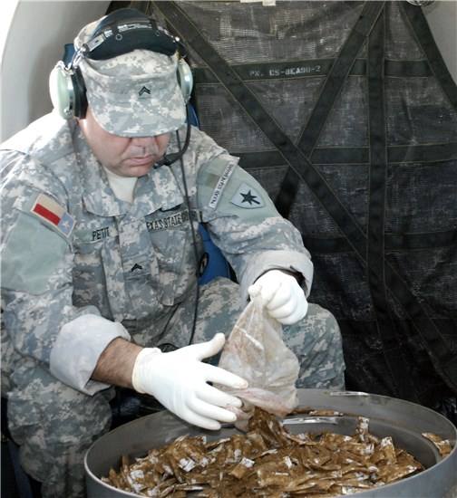 Private Paul Pettit, 3rd Battalion, 1st Regiment, Texas State Guard, unloads a bag of bait to be dropped over the South Texas Zapata area during the 2012 Texas Oral Rabies Vaccination Program.