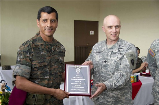 U.S. Army Lt. Col. Anthony Flood, commander 1st Squadron, 124th Cavalry Regiment, Texas Army National Guard, presents National Army of Guatemala Brig. Gen. Antonio Lopez, commander of the Interagency Task Force Tecun Uman, with a plaque for his unit's successful training.