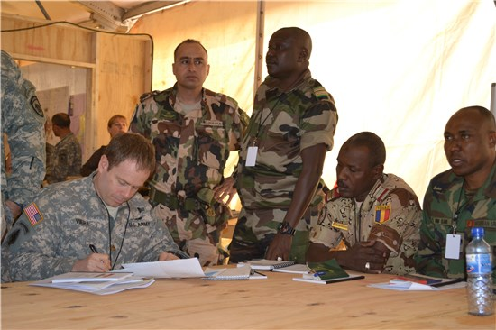 Maj. Sean Vieira, Special Operations Detachment planner, works to develop campaign plans with African counterparts during the 2014 FLINTLOCK exercise in Niger.