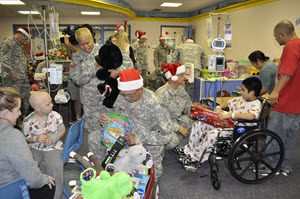 Guardsmen from the19th Regiment, Texas State Guard (TXSG), provide toys to children during the holidays at Medical City Children's Hospital in Dallas, Dec. 13, 2014. The toy donation was a part of the TXSG's Young Heroes of the Guard toy drive. Thanks to generous donations from Texas guardsmen and members of the community, over 3,500 toys were delivered to three different hospitals in Dallas during the holidays: Children's Medical Center of Dallas, Medical City Children's Hospital, and Our Children's House of Baylor. (Texas State Guard photo by Capt. Esperanza Meza/Released)