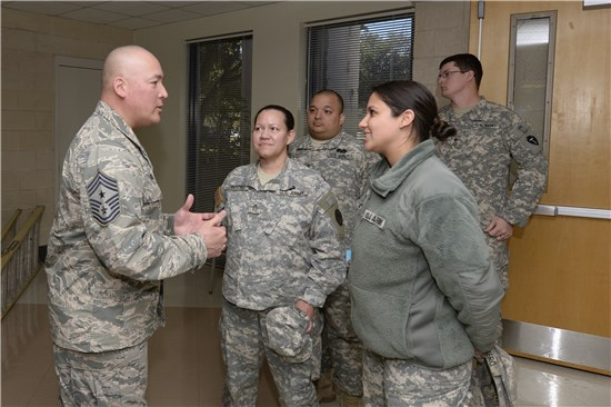 National Guard Bureau senior enlisted leader Command Chief Master Sgt. Mitchell Brush takes time to meet with Staff Sgt. Nayda Troche, center, and Spc. Jennifer Cubero, Texas Medical Command, Texas Army National Guard, after his town hall meeting held at Camp Mabry in Austin, Texas, Feb. 9, 2014.