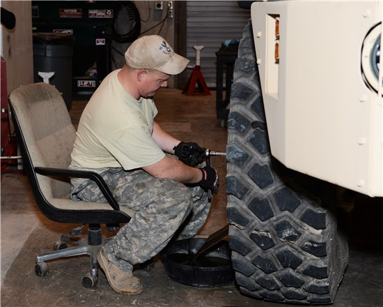 Sgt. Michael Shelby, Maneuver Area Training Equipment Site (MATES), Texas Army National Guard, works on a heavy equipment transporter, while using a drip pan to maintain leaking gear oil.