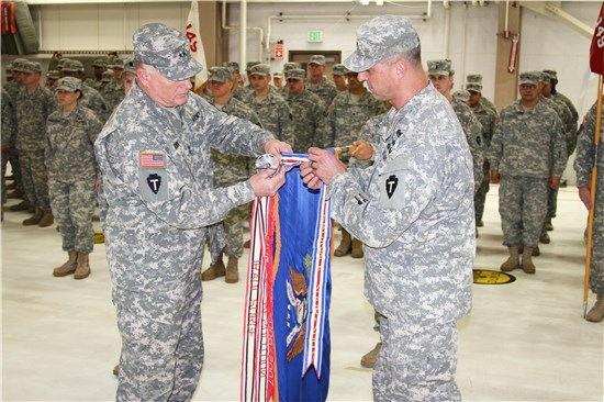 "Maj. Gen. James K. ""Red"" Brown, commander of the 36th Infantry Division, and Col. Rick Adams place the Valorous Unit Award on the ""colors"" of the 1-149th Attack-Reconnaissance Battalion during a ceremony held at Ellington Field."