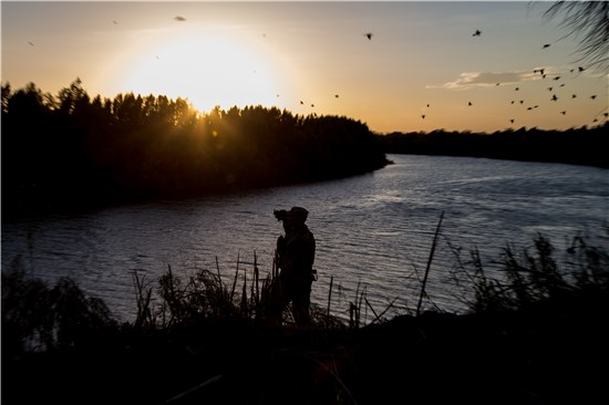 A soldier from the 36th Infantry Division, Texas Army National Guard observes a section of the Rio Grande River at sunset.