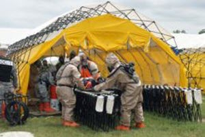 Courtesy Photo Guardsmen with the Texas National Guard's 836th Chemical Company, 6th Chemical, Biological, Radiological, Nuclear, and High-Yield Explosives (CBRNE) Enhanced Response Force Package, Joint Task Force 136 (Maneuver Enhancement Brigade), move an injured civilian into a chemical decontamination line during a training exercise at Govalle Waste Water Treatment Plant in Austin, Texas, as part of their weeklong annual training period April 22, 2015. (U.S. Army National Guard photo by Spc. Martha Guerrero/Released)