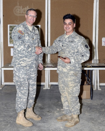 1st Lt. Alicia Lacy Spc. Jordan Norkett, C Troop, 1-124 Cavalry Regiment, 56th Infantry Brigade Combat Team, 36th Infantry Division, Texas Army National Guard, receives the second place novice award from Maj. John B. Conley following the Texas Military Forces' Governor's 20 Sniper competition Feb. 22, 2015, at Camp Swift near Bastrop, Texas. Only one team of two, a sniper and a spotter, can make up the Governor's 20.