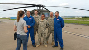 A meteorologist interviews members of Texas Task Force 1 and the Texas Army National Guard at the Army Natioanl Guard aviation support facility, in Grand Prairie, Texas, May 17, 2015. The combined team rescued a couple in distress early in the day and brought them to safety. (U.S. Air National Guard photo by Senior Master Sgt. Elizabeth Gilbert/Released)