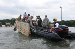 Capt. Maria Mengrone Texas Army National Guard soldiers on state active duty, conduct critical water rescue rehearsals with first responders from Texas Task Force 1 (TXTF-1), while on standby to respond to flooding in the North Texas region, May 16, 2015. Guardsmen provided light medium tactical vehicles to emplace TXTF-1 inflatable boats in flood waters to simulate potential flood victim rescues in controlled conditions. Guardsmen often work side by side with local and state partners to help Texans in need during disaster situations. (U.S. Army National Guard photo by Capt. Maria Mengrone)