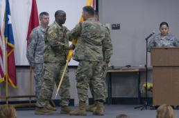 Sgt. Josiah Pugh Brig. Gen. Sean A. Ryan passes the colors from the 136th Regiment's outgoing commander, Col. Michael Adame, to the unit's incoming commander, Col. Carlton Smith, during a change of command ceremony held at the Camp Mabry Simpson Auditorium on April 14, 2016. The ceremony represents the change of responsibility from one commander to another. (U.S. Army National Guard photo by Staff Sgt. Josiah Pugh)