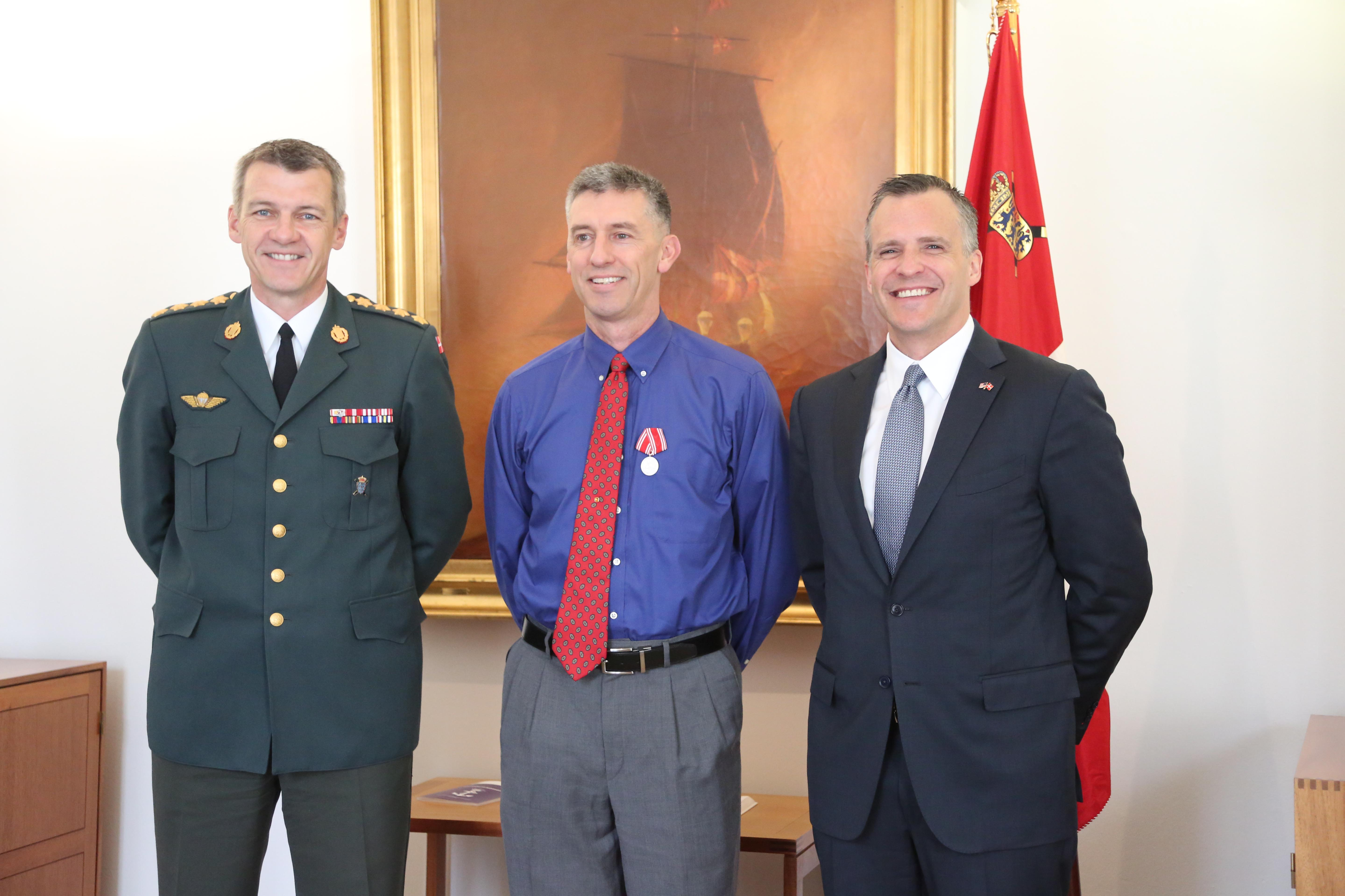 CAPTION:  Capt. Bradley Grimm, center,Texas Army National Guard, receives the Danish Defense Medal for Special Meritorious Efforts by Danish Defense Gen. Peter Bartram, left, and American ambassador to Denmark Rufus Gifford, right, at a ceremony held in Denmark, April 19, 2016.  Grimm was instrumental in foiling a terrorist plot to bomb a Danish school and assisted Danish security forces in making an arrest. (Danish Military photo by Sune Wadskjær/Released)