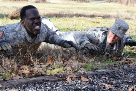 Staff Sgt. Timothy Boutte, the senior mechanic for Company D, 949th Brigade Support Battalion, 56th Infantry Brigade Combat Team, 36th Infantry Division, Texas Army National Guard, pushes through prone rows while Command Sgt. Maj. Michelle Thompson, the battalion's command sergeant major, motivates him to complete the air assault course at Camp Swift, Jan. 8. The course was one of eight events that were part of the 56th Infantry Brigade Combat Team's Best Warrior Competition. (U.S. Army National Guard photo by Sgt. Michael Vanpool/Released)