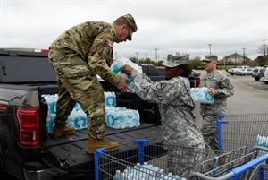 Maj. George Hurd, left, Staff Sgt. Erdoo Thompson, center, and 1st Lt. Matthew Verdugo, right, all of the 136th Maneuver Enhancement Brigade, load bottled water in preparation for Hurd's convoy to Flint, Michigan, March 10, 2016, in Round Rock, Texas. (Photo by Master Sgt. Daniel Griego)