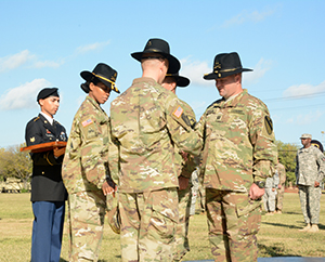 U.S. Army Capt. Lucas Hamilton, commander 249th Transportation Company, receives his cavalry Stetson from Lt. Col. Daryl Morse, commander Special Troops Battalion, 1st Cavalry Division Sustainment Brigade during a patch-over ceremony held on Fort Hood, Texas. (U.S. Army photo by Sgt. James Strunk Released) Photo cropped to highlight subjects, 161016-Z-IX228-563PS