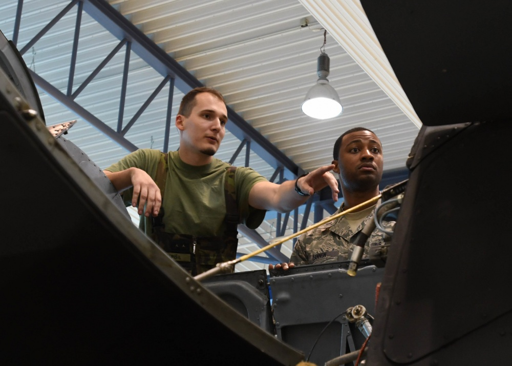 U.S. Air Force 1st Lt. Tyson Cannon, maintenance operations officer with the 149th Fighter Wing, Texas Air National Guard, and Czech Air Force 1st Lt. Pavel Popspisil, chief of electric and special equipment group, examines the main gear box of the Mi-24 Hind Attack Helicopter March 22, 2017 at 22nd Air Base, Namest Nab Oslavou, Czech Republic. Popspisil explained how the gear box and engine were configured and removed. (Air National Guard photo by Senior Airman De'Jon Williams)