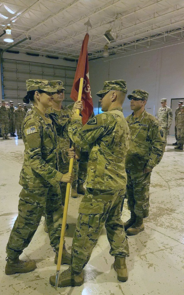 Courtesy Photo | Texas Army National guardsmen Capt. Amanda Windle (left), the incoming commander of the 936th Engineer Company, receives the company guidon from Lt. Col. Matthew Calton (center), 111th Engineer Battalion Commander, 176th Engineer Brigade while outgoing commander Capt. Eric Burnett (right) and 1st. Sgt. Denton Humphery look on. Windle became the first female commander of a Sapper unit in the Texas Army National Guard the unit is based in San Angelo, Texas, June 11, 2017. (U.S. Army National Guard photo by Courtesy Photo)