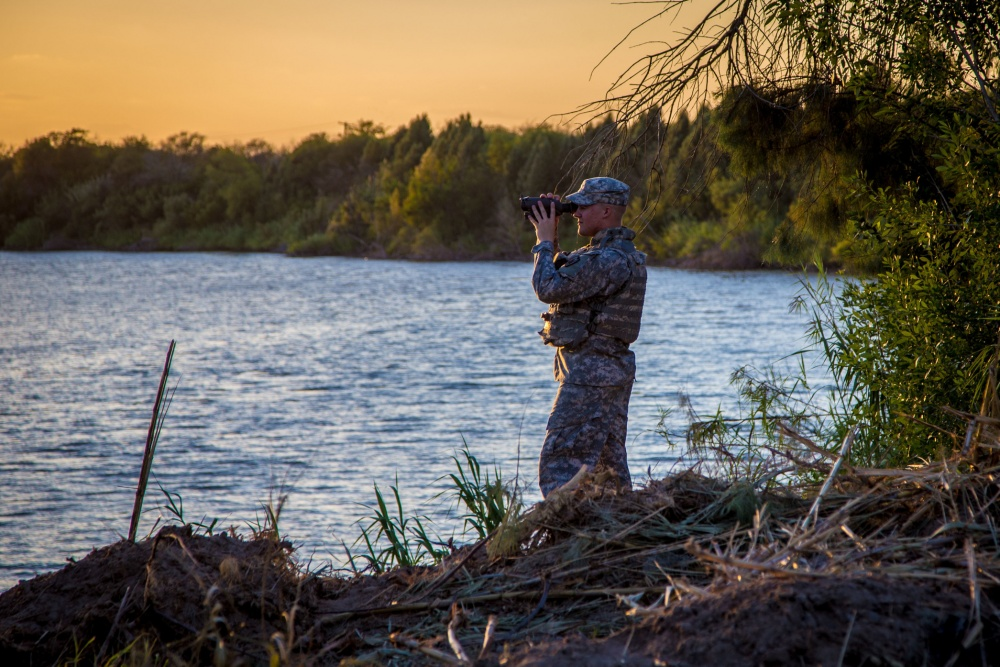 Texas Army National Guard Soldier observes a section of the Rio Grande River, along the Texas-Mexico border. The Texas Military Department's mission in support of Operation Strong Texas transitioned from an operational state active duty mission to a federal Title 32 training mission, July 2017. (U.S. Army National Guard photo by Maj. Randall Stillinger)
