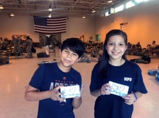 Photo By Capt. Aaron Moshier | Fatima Maniar's son Gabriel and Nichole Bode's daughter Gabbie, volunteers from the St. Thomas More Catholic Church and School, pose for a photo with handmade thank you notes for soldiers serving out of the Rosenberg National Guard Armory. Volunteers washed more than 100 loads of laundry as a show of support and appreciation for mobilized Soldiers assisting in Hurricane Harvey relief efforts, Rosenberg, Texas, September 2, 2017.