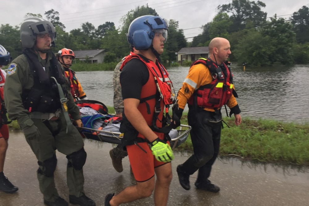 Photo By Capt. Martha Nigrelle | Texas National Guard soldiers, service members from the U.S. Coast Guard and Texas Task Force 1 and Austin-Travis County Emergency Medical Service swift water rescue technicians work together to rescue a man with special medical needs from high-rising waters and medically evacuate him to a safe location, in Orange, Texas, August 30, 2017. Thousands of first responders from the military and local, state and federal agencies joined together to render aid to all those endangered by the high-rising floodwaters in south Texas following Hurricane Harvey. (U.S. Army National Guard photo by Capt. Martha Nigrelle)