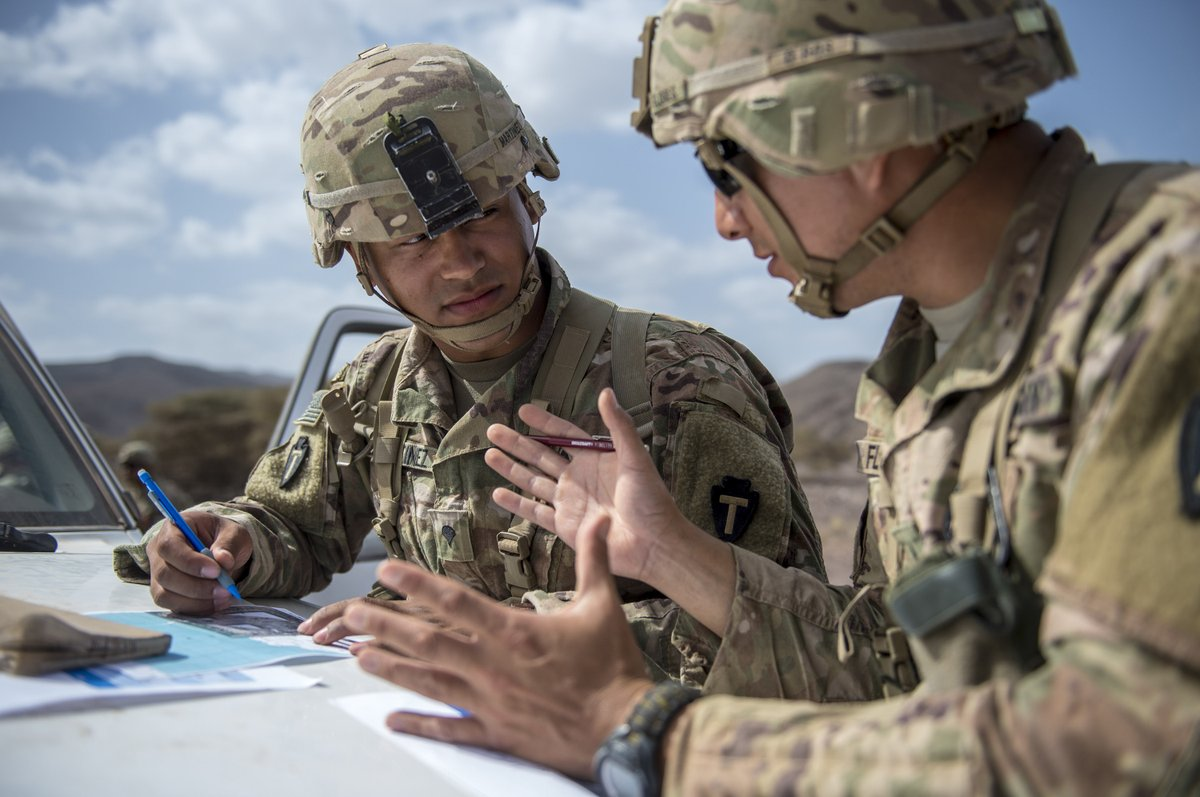 Photo of two soldiers outside planning while using the front of a vehicle as a writing surface.