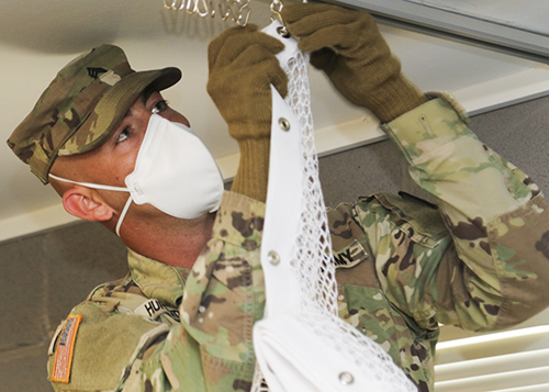 Texas Army Sgt. Keith Huffstuttler, a team leader with Task Force 176's 840th Engineering Mobility Augmentation Company, installs curtains to separate beds in Camp Swift barracks to adapt them into medical isolation support facilities in Bastrop, Texas, on April 17, 2020. The TMD has established this isolation facility for Soldiers, Airmen and State Guardsmen suspected of having COVID-19 so that they may recover in a safe environment and prevent further spread of the virus. (U.S. Army National Guard photo by Staff Sgt. Michael Giles)