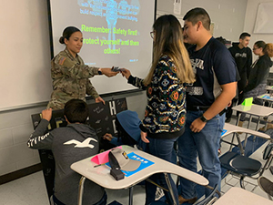 U.S. Army Spc. Maritssa Quintanilla hands markers to a student at Pharr-San Juan- Alamo Early College High School in San Juan, Texas Jan. 31, 2020.