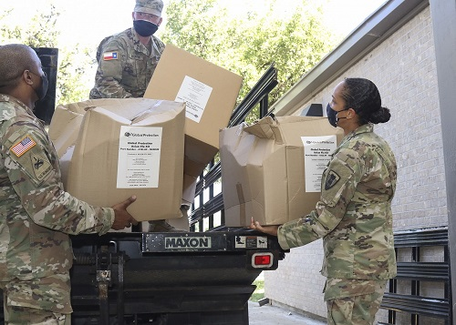 Members of the Texas Military Department's Joint Task Force 176—Texas State Guard Pfc. Jason Hunter, Texas National Guard Capt. Stephanie Enloe, the task force's medical operations officer, and Sgt. 1st Class Rajendran Kumaraswamy, the task force's medical noncommissioned officer—unload disinfecting kits for Soldiers preparing to support long-term care facility disinfection operations at Camp Mabry, in Austin, Texas, May 7, 2020. Joint Task Force 176, a unit of Texas Military Department personnel who have been distributing food and supplies during the COVID-19 pandemic, are now preparing to support the Texas Division of Emergency Management in disinfecting long-term care facilities. (U.S. Army National Guard photo by Staff Sgt. Michael Giles, 36th Infantry Division Public Affairs)