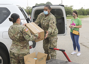 Army National Guard Spc. Jessenia Cano, an automated logistical specialist, and Spc. Tesely Cooley, a petroleum supply specialist, both with the 449th Aviation Support Battalion and assigned to Joint Task Force 176, load personal protective equipment into the vehicle of a medical provider in Austin, Texas, July 1, 2020. General Support Unit 18 is a team of Texas Military Department personnel assigned to Joint Task Force 176 who activated to help distribute medical supplies to health care providers during the COVID-19 pandemic. (U.S. Army National Guard photo by Staff Sgt. Michael Giles, 36th Infantry Division Public Affairs)