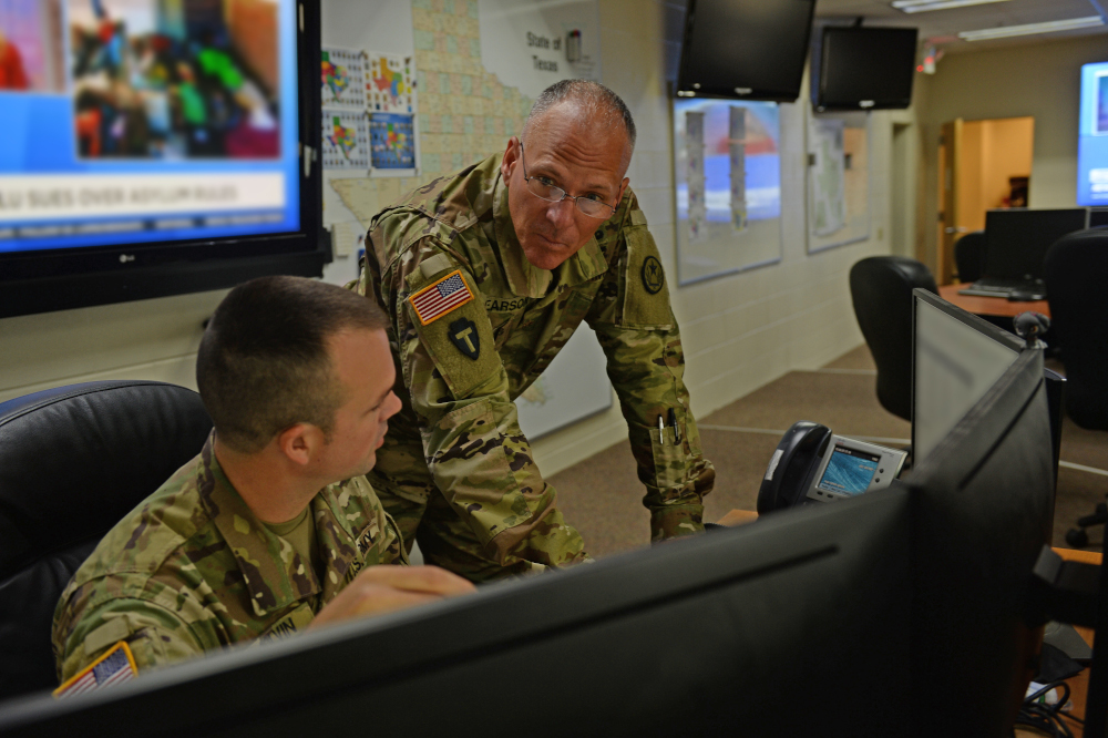 Sgt. Kory Colvin, left, and Maj. John Pearson, right, monitor real-time updates in the Texas Military Department Joint Operations Center, Camp Mabry, Austin, Texas. The JOC serves as a link between partner agencies and Texas' 24,000 Guardsmen and civilians.