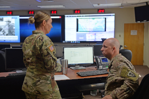 Staff Sgt. Kimberly Eastburn, left, and Sgt. 1st Class Clinton Staha, right, discuss a potential unit mobilization in response to flooding at the Texas Military Department Joint Operations Center at Camp Mabry in Austin, Texas.