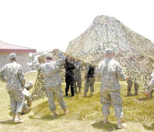 "Guard members rehearse setting up a ""shade structure."" The camo netting significantly cools an area even in the hottest sun allowing guard members to set up a command post or temporary office in even the most barren terrains."
