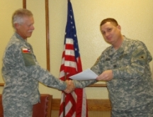 Maj. Roger Vertrees of the TMB receiving Meritorious Service Ribbon from Capt. Alec Ross Photo by 2LT Tom Goff