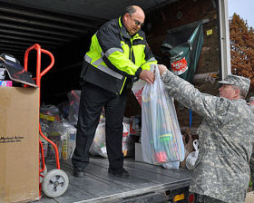 Officer Mark Calvert, left, takes a bag of toys from Corporal Wells of the Texas State Guard, Wednesday at police headquarters. Members of the Guard donated 300 toys to Santa Cop.