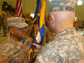 Photo of MAJ Alfred Sustaita, Jr., recieving the colors from COL Frank Woodall