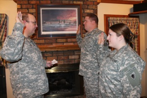 (Left to right) Chief Warrant Officer James Smith swears in PFC Andy Ritter into the Texas National Guard and PV2 Amanda Ritter into the Texas State Guard on January 5, 2014. Photo by CW2 Janet Schmelzer, PAO, 4th Regiment.
