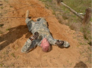 After successfully clearing the low-crawl obstacle on his stomach, Officer Candidate Michael Ross goes for round 2 on his back. Photo Credit Captain Shaw James