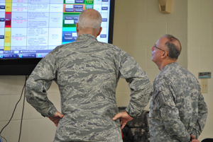 Texas State Guard officers 1st Lt. Carl Mathews, 447th Support Group, 5th Air Wing, and Capt. Joseph Conte, 8th Regiment,   review the emergency operations command information board at the 8th Regiment tactical operations command center