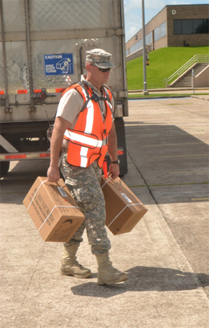 Pfc. Justin Stanton, 8th Regiment, Texas State Guard, carries cases of ready-to-eat meals for residents of Brazoria County