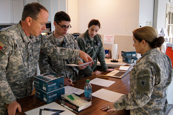 Staff Sgt. Michael Mills, Spc. Adam Poncher, Spc. Kelly Bach, and 1st Lt. Lana Cameron, 2nd Regiment, Texas State Guard, review registration documents at the mass care shelter at St. Luke's Episcopal Church in Stephenville, Texas, January 22, 2016.  Mass care sheltering is an essential skill that the Texas State Guard can provide to assist local residents during an emergency. (Photo by Spc. Stefan Wray, 2nd Regiment/ Released)